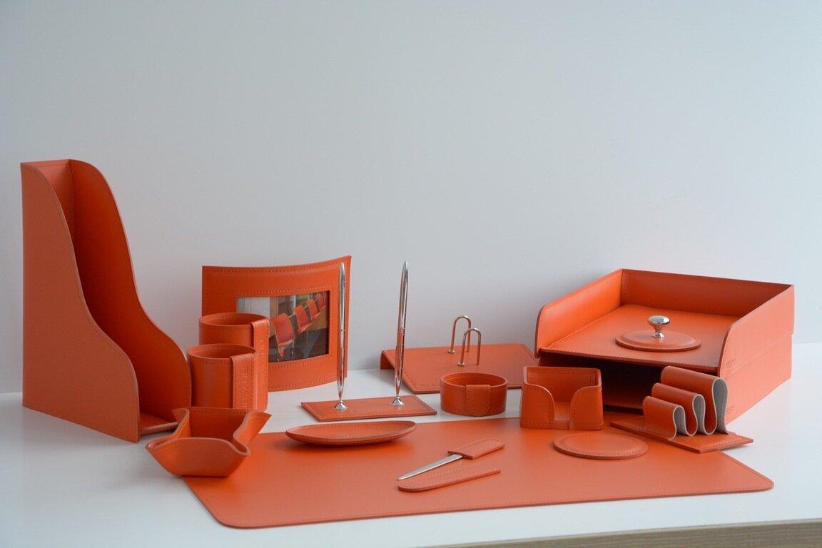 Настольный кожаный набор оранжевого цвета. В комплект входит бювар (скругленный прямоугольник), горизонтальные лотки, лотки для мелочей, вертикальный лоток, канцелярские стаканы и другие полезные мелочи